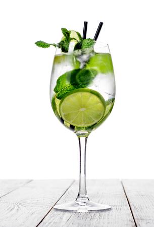 Cocktail in glas wijn gemaakt met champagne, frisdrank, limoen met munt op een witte achtergrond.