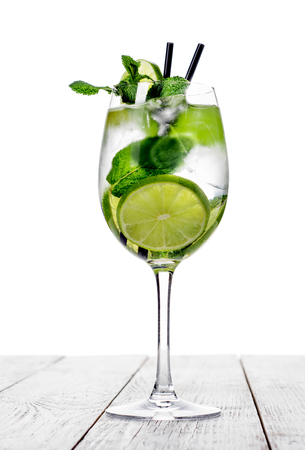 Cocktail in wine glass made with champagne, soda, lime with mint on white background.