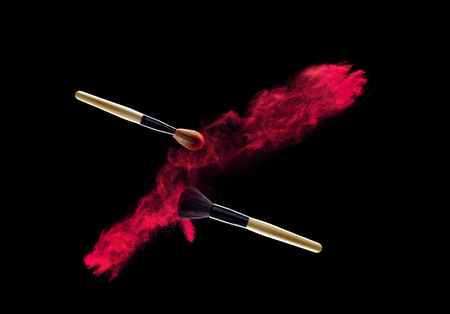 Make-up brush with powder explosion on black background.