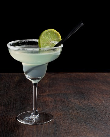 rimmed: margarita cocktail with lime on dark background