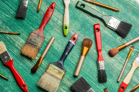 gloss: make-up brushes with paint brushes on wooden background. Flat lay