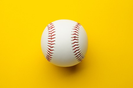 Baseball ball on yellow background with copy space Stock Photo