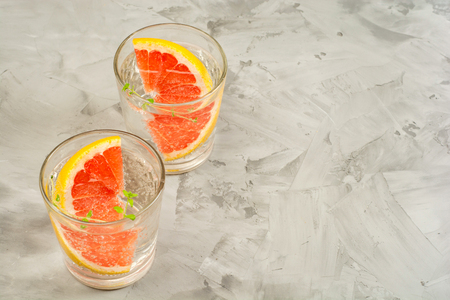 Grapefruit lemonade. Two glasses of detox drink, water with grapefruit, rosemary branches and ice. Recipe concept, cocktail.