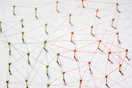 Linking entities. Network, networking, social media, internet communication abstract. A small network connected to a larger network. Web of gold wires on white wooden background. Network hub or key person.