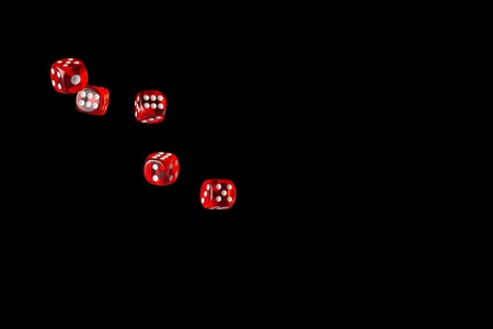 Gambling game. Rolling red dice isolated over black background with copy space. 免版税图像