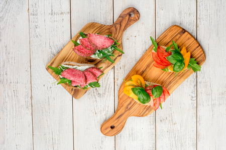 Variety of mini sandwiches with cream cheese, vegetables and salami. Sandwiches with cheese, tomato, salami, basil, on a light background, top view. Flat lay. Banco de Imagens
