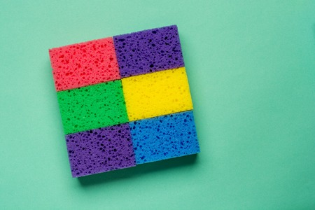 Set multi-colored sponges on a green background, space for text. Flat lay.