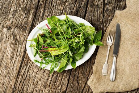 Healthy fresh green salad leaves on plate with cutlery on rustic wooden background. Stockfoto