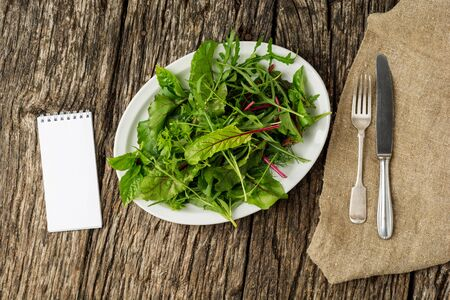 Fresh salad plate with mixed greens (arugula, mesclun, mache) on dark wooden background with cutlery and notepad. Healthy food. Green meal. Flat lay Stock fotó