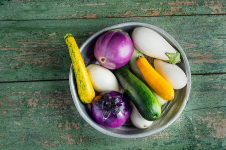 Fresh eggplants and zucchini in basket over wooden green background. Flat lay. Healthy food or diet.