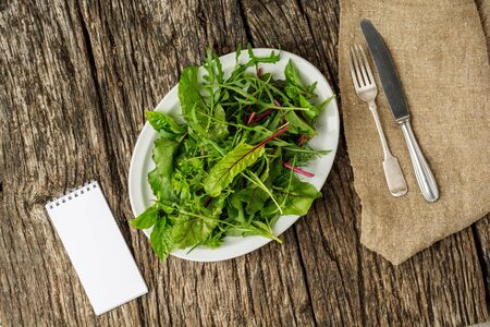Flat lay. Fresh salad plate with mixed greens on dark wooden background with cutlery and notepad. Healthy food. Green meal. Stock fotó