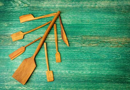 Christmas tree made from wooden kitchen tools on green wooden background with copy space. Flat lay background