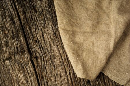 Burlap texture on rustic wooden table background. Free space for text. Flat lay.