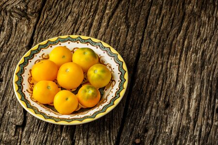 Fresh, organic yellow tomatoes on yellow plate over rustic wooden background with copy space. Flat lay