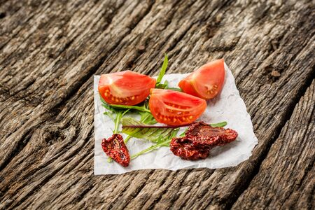 Fresh and sun dried tomatoes on wooden rustic background with copy space, top view or flat lay. Minimal composition Stock Photo