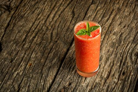Glass of fresh tomato juice on a wooden board with free space. Stock Photo