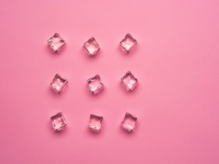 Ice cubes on pink background. Flat lay