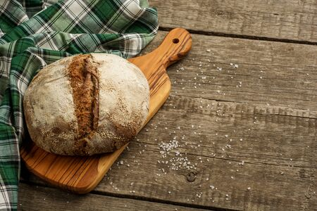 Freshly baked traditional bread on wooden table with salt. Zdjęcie Seryjne