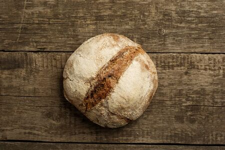 Freshly baked traditional bread on rustic wooden background. Flat lay or top view.