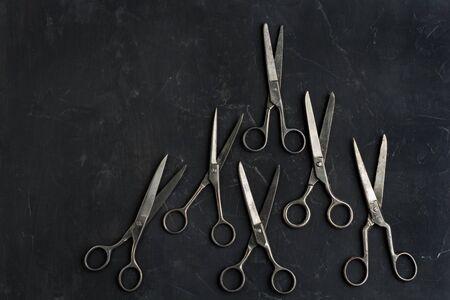 Old scissors on dark background . Minimal black. Flat lay