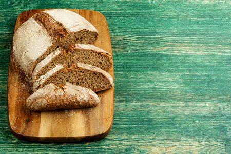 Yeast free, no knead, unleavened healthy organic rye wheat half sliced homemade bread loaf on kitchen board on green wooden table. Zdjęcie Seryjne