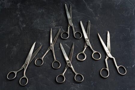 Many scissors on dark background . Minimal black. Flat lay Zdjęcie Seryjne