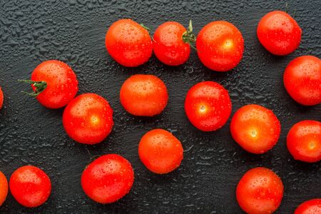 Fresh cherry tomatoes on a black background with water drops. Top view or flat lay. Minimal black stile.