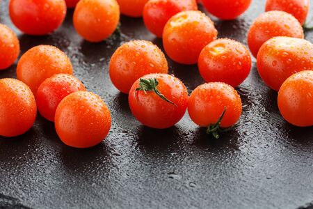 Fresh cherry tomatoes on a black slate background with water drops. Minimal black
