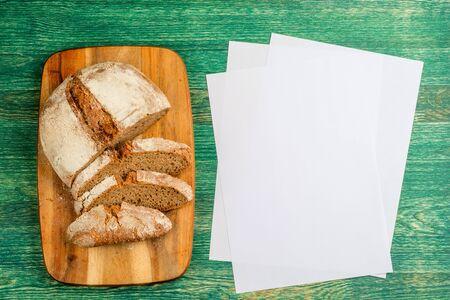 Yeast free, no knead, unleavened healthy organic rye wheat half sliced homemade bread loaf on kitchen board on green wooden table Zdjęcie Seryjne