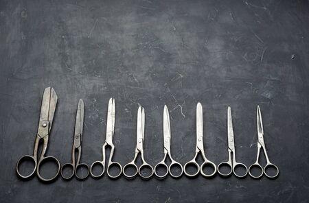 Many different scissors on dark background. Minimal black. Flat lay. Zdjęcie Seryjne