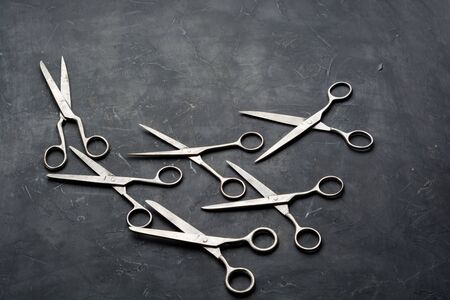 Old scissors on dark background with copy space. Minimal black.