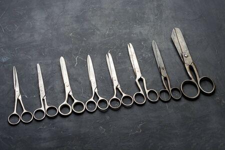 Many different scissors on dark background. Minimal black. Flat lay