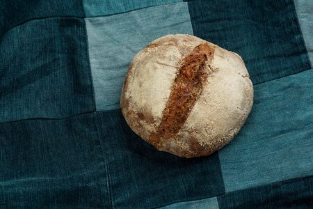 Traditional black rye-bread on denim background with copy space.