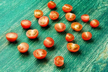 Fresh ripe organic Cherry Tomatoes on green wooden background.