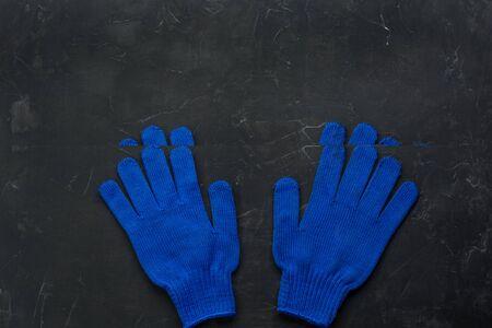 Blue working gloves over dark background, construction tools. Minimal black.