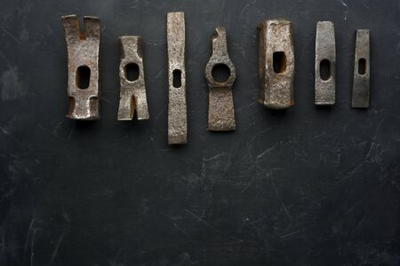 Old rusty hammers on dark background with place for text. Minimal black. Zdjęcie Seryjne