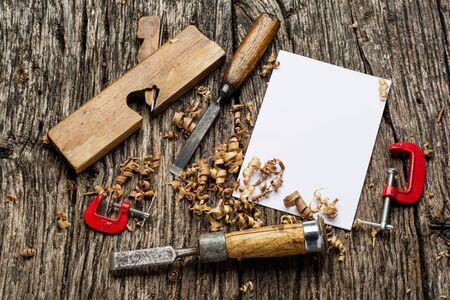 Blank business card on wooden table with carpenter tools and sawdust top view.