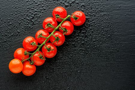 Fresh cherry tomatoes on a black background with water drops. Top view or flat lay. Minimal black stile