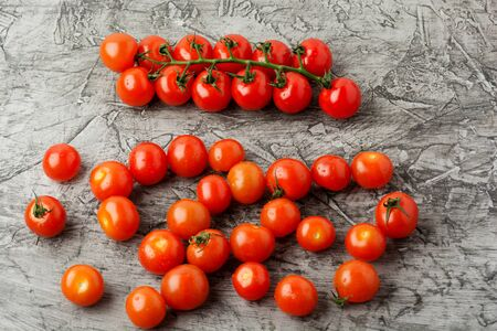 Group of cherry tomatoes on a gray concrete background. Ripe and juicy cherry tomatoes