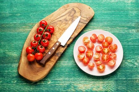 Fresh tomatoes with a knife . On green rustic background. Zdjęcie Seryjne