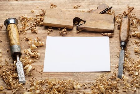 carpenter tools on dark rustic table with blank paper.