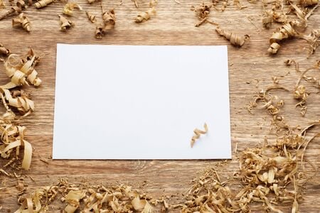 wood shavings on a wooden background with blank paper. Zdjęcie Seryjne