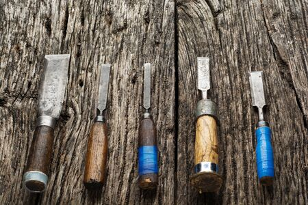 Carpenter tools composition. Old carpenter chisels laying on rustic wooden table upper view. Zdjęcie Seryjne