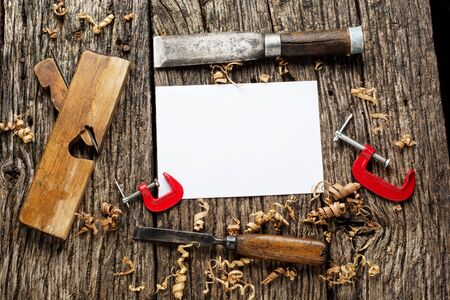 Old carpenter tools on rustic wood table with blank paper top view.