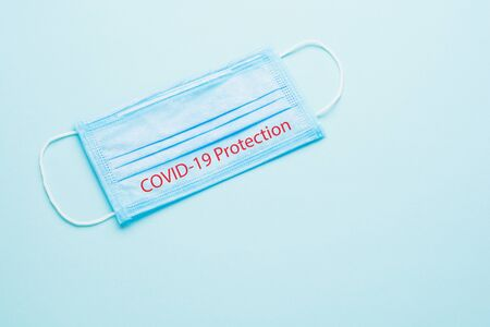 Blue Medical Disposable Face Mask with covid-19 printed on it. Coronavirus pneumonia gets official name from WHO: COVID-19. Disposable breath filter face mask with earloop.