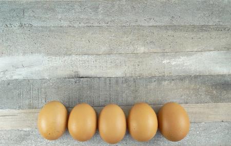 Brown chicken eggs at wooden background
