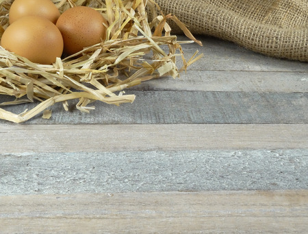 Chicken eggs in nest with burlap over wooden background