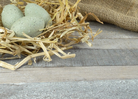 Stone Gray decoration eggs with straw on burlap over wooden background