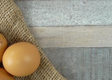 Brown chicken eggs on burlap over wooden background