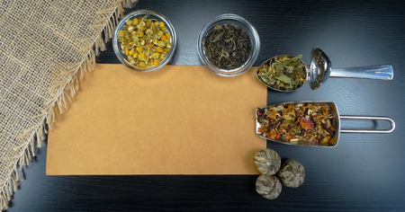 Tea assortment with tea and flowers on wooden background